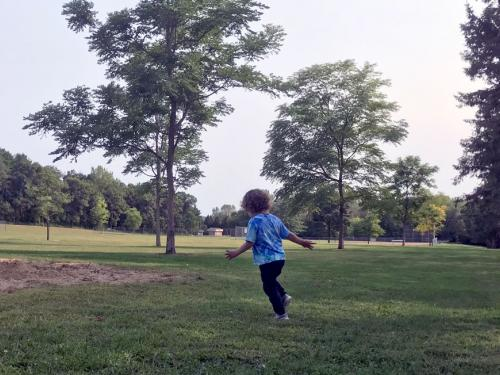 Child runs in park field