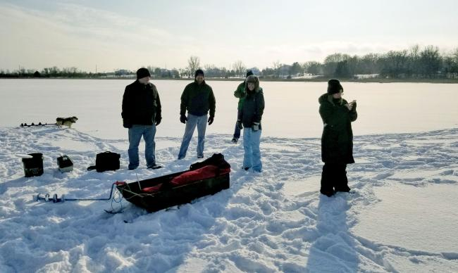 Four people on a frozen lake