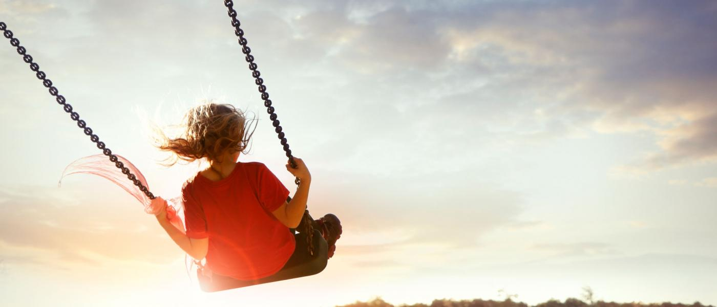 Girl on a swing at sunset