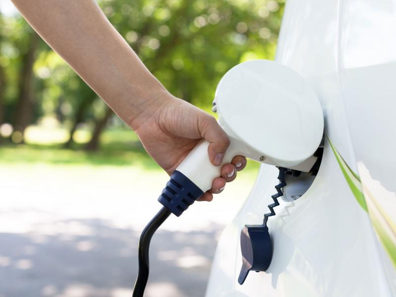 Close up of hand charging electric vehicle
