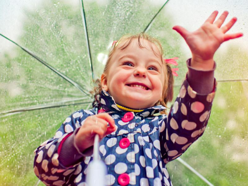 Girl with umbrella smiles and reaches out
