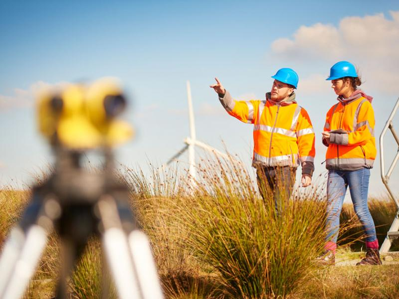 Two workers walk near wind turbine