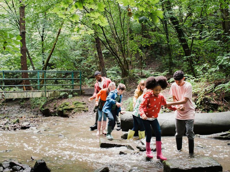 Kids and adults cross a stream