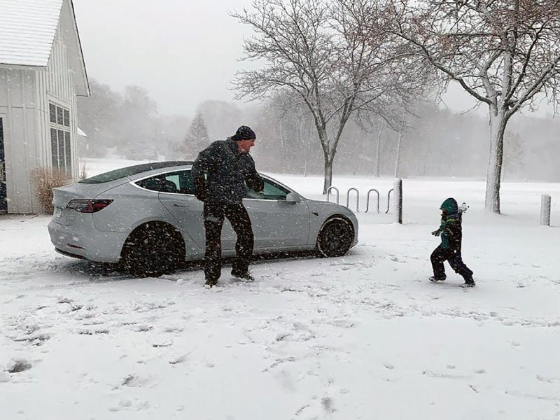 Dad and kid play in snow near parked car