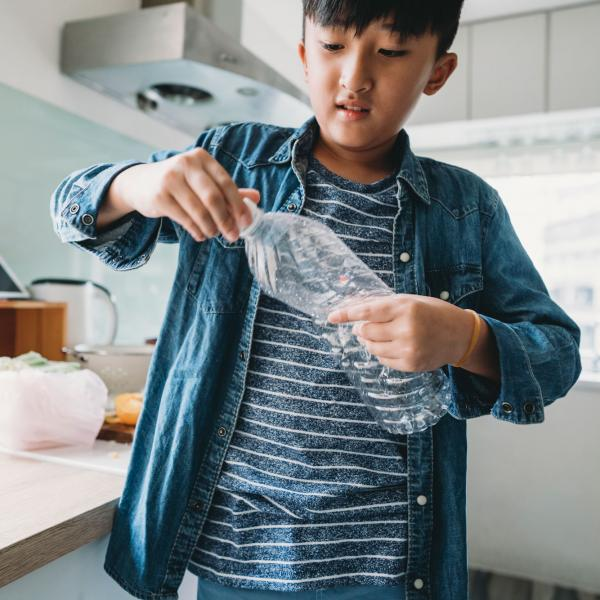 Boy with plastic bottle in kitchen
